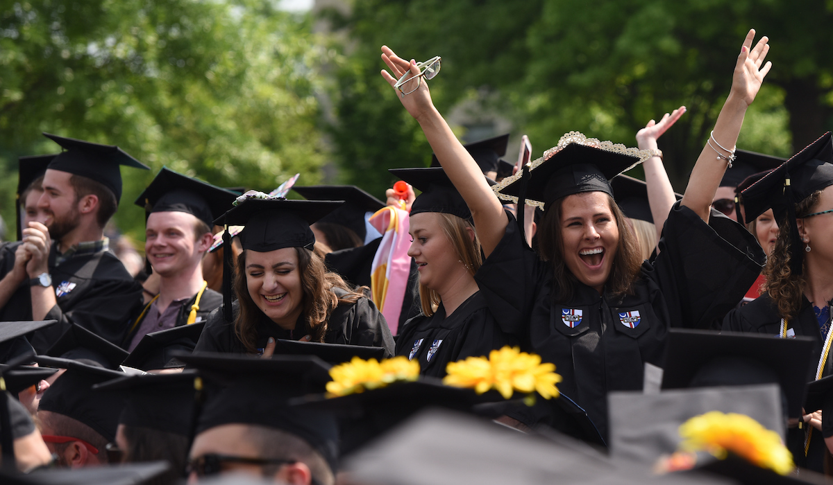 Female graduate cheering in celebration of Commencement